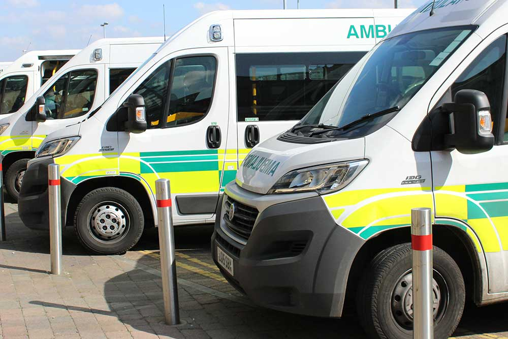 A row of patient transport ambulances outside Queen's Hospital