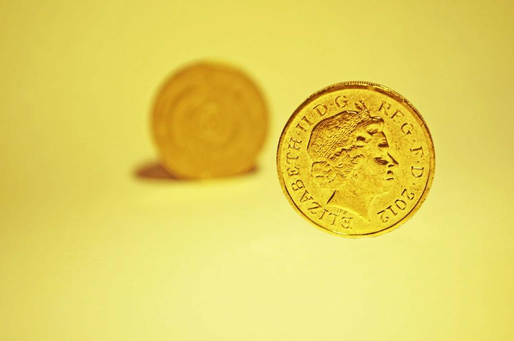 Pound coin on a yellow background