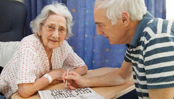 Patient and visitor filling in a cross word