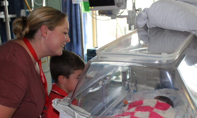 Frances and Henry look into the incubator of a baby on the unit