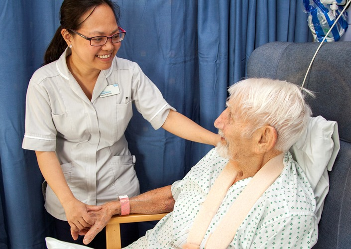 Healthcare assistant and patient on the ward