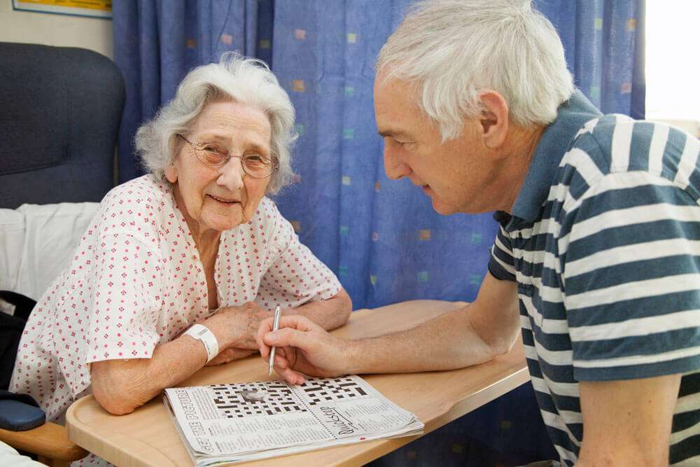 man visiting patient doing a crossword