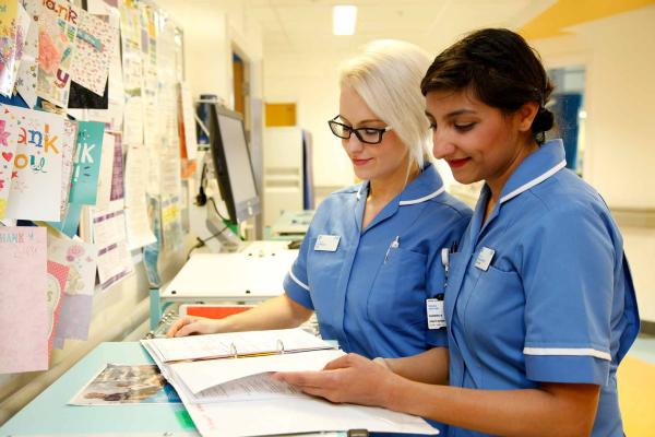 Two nurses smiling doing work
