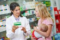 A pharmacist speaking to a woman holding a baby